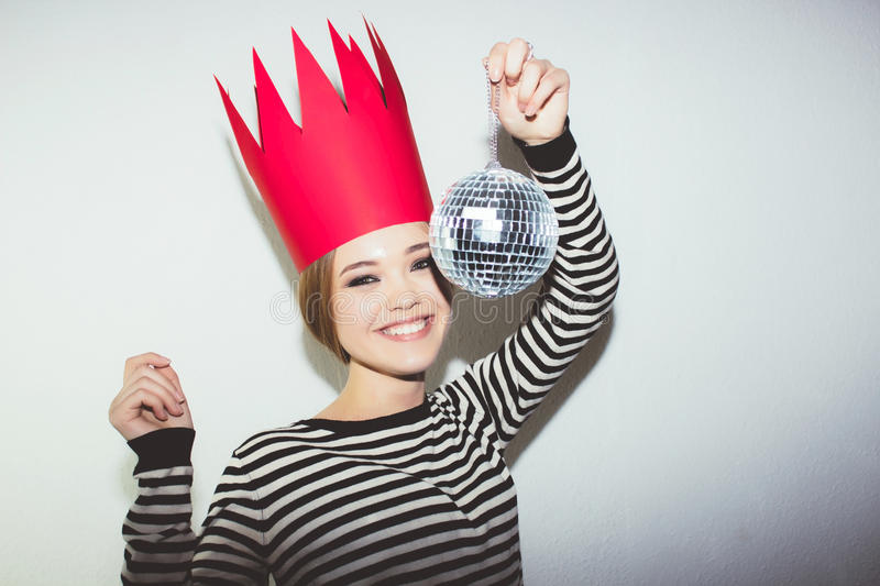 Young smiling woman celebrating party, wearing stripped dress and red paper crown, happy dynamic carnival disco ball. Young smiling woman on white background stock photography