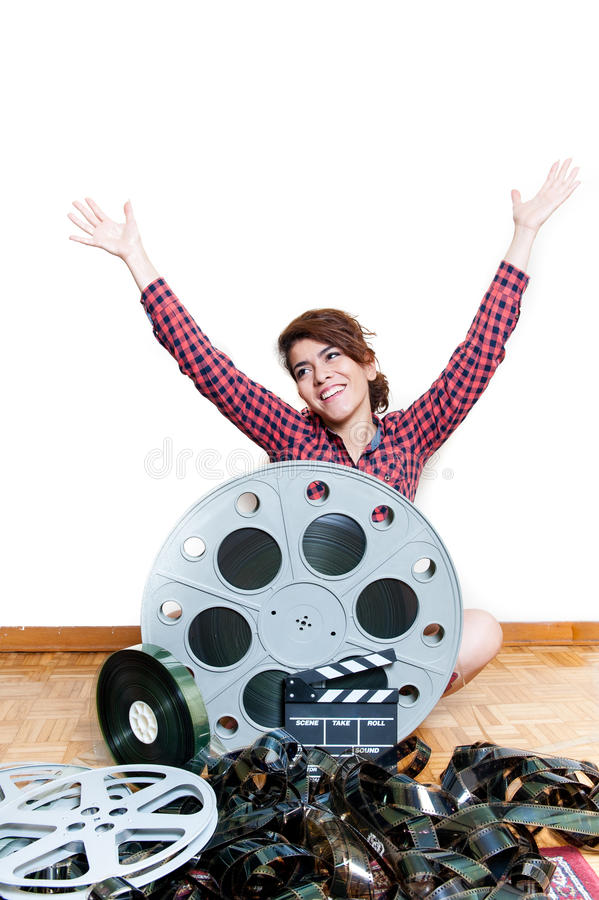 Young smiling woman with cinema movie reels arms up stock photo