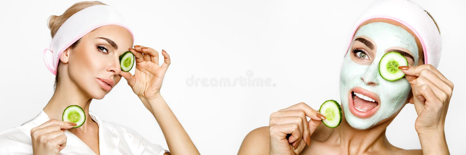 Young smiling woman with a clay mask. Photo of attractive young woman covering her eyes with cucumbers on a white background. stock photo