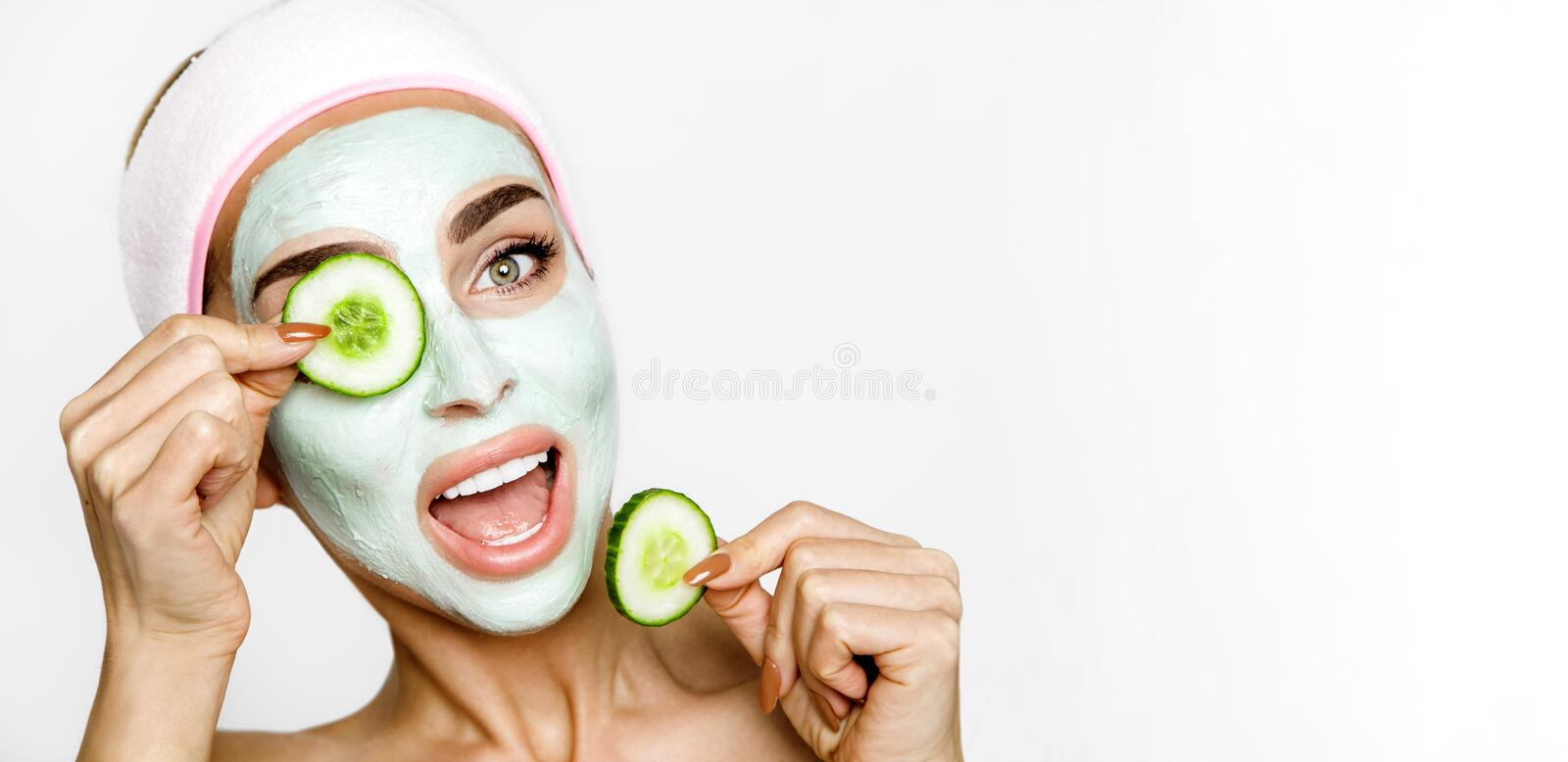 Young smiling woman with a clay mask. Photo of attractive young woman covering her eyes with cucumbers on a white background. royalty free stock photography
