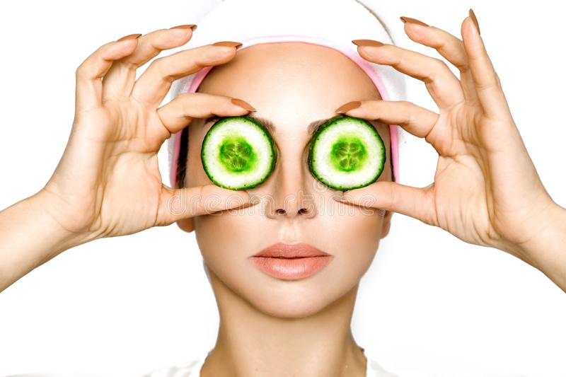 Young smiling woman with a clay mask. Photo of attractive young woman covering her eyes with cucumbers on a white background. royalty free stock images