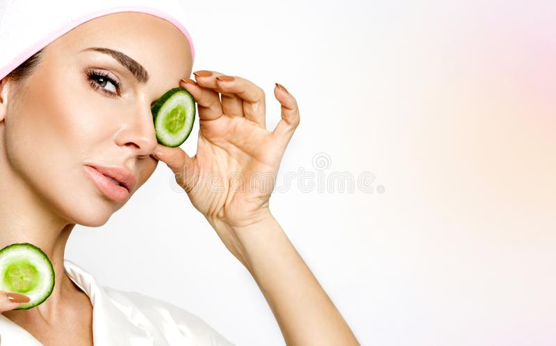 Young smiling woman with a clay mask. Photo of attractive young woman covering her eyes with cucumbers on a white background. stock photography