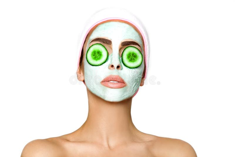 Young smiling woman with a clay mask. Photo of attractive young woman covering her eyes with cucumbers on a white background. royalty free stock photo