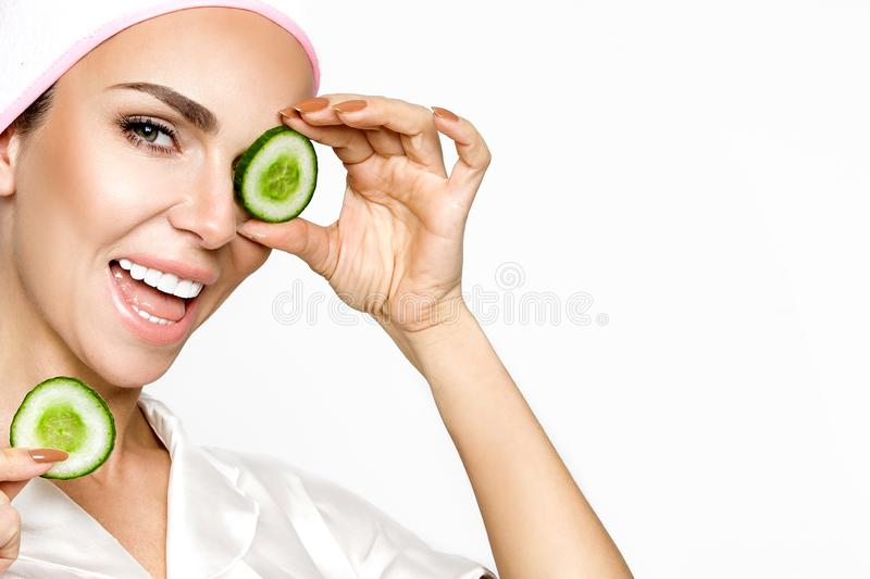 Young smiling woman with a clay mask. Photo of attractive young woman covering her eyes with cucumbers on a white background. royalty free stock image