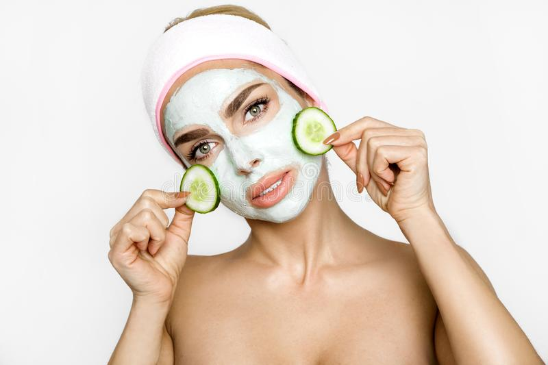 Young smiling woman with a clay mask. Photo of attractive young woman covering her eyes with cucumbers on a white background. stock images