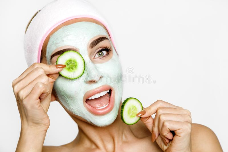 Young smiling woman with a clay mask. Photo of attractive young woman covering her eyes with cucumbers on a white background. stock photos