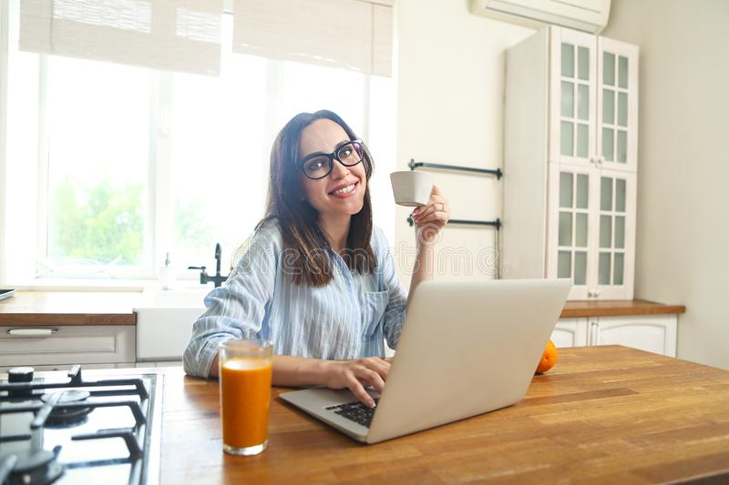 Young smiling woman with computer and cup of coffee at the kitchen royalty free stock photography