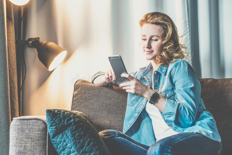 Young smiling woman in denim shirt sitting at home on couch and using smartphone. Girl uses digital gadget. royalty free stock photography