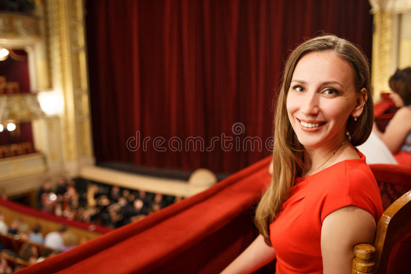 Young smiling woman in dress sitting in theatre royalty free stock images