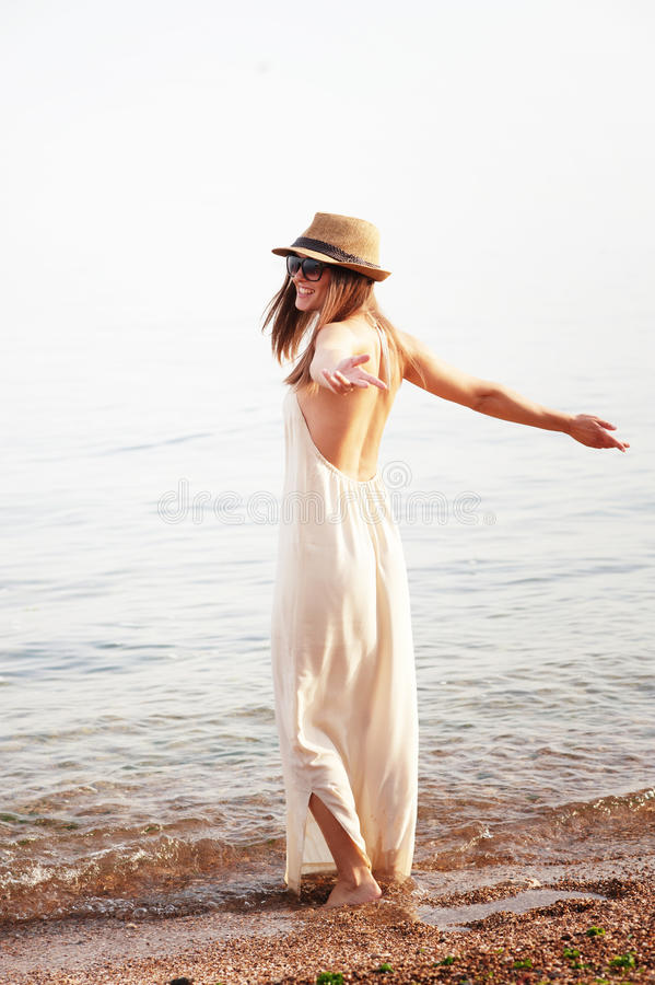 Young smiling woman enjoy summer holidays on a sea beach. Long white dress with open back and hat royalty free stock photos