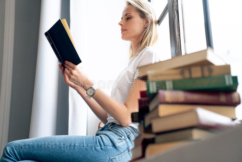 Young smiling woman enjoying new bestseller book sitting on window sill, happy book lover reading fiction literature relaxing at. Home, student teenager study stock image