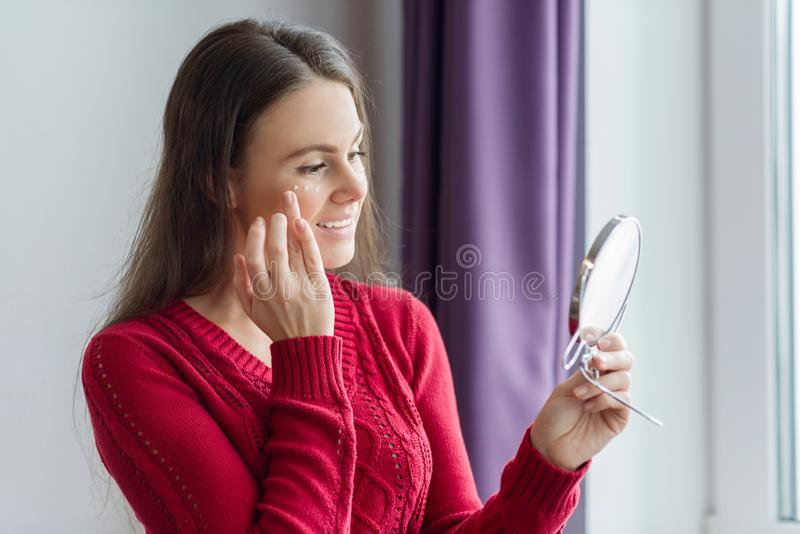 Young smiling woman with face moisturizer near eyes, female holding face cream, standing near window with mirror. Youth and skin c royalty free stock image