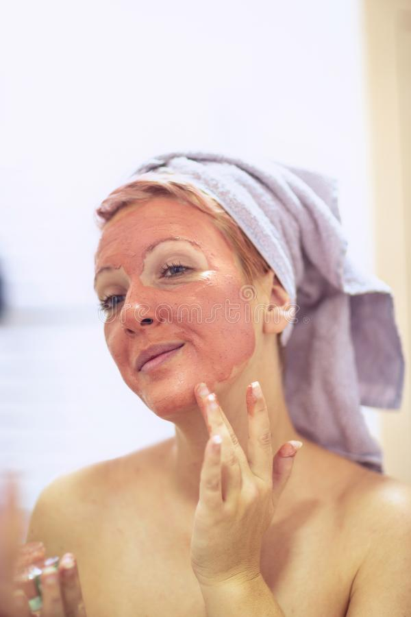 Smiling woman with a facial mask - Skincare and cosmetics concept stock image