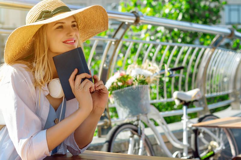 Happy blonde woman is reading book and dreaming royalty free stock image