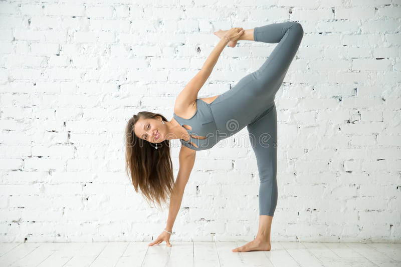Young smiling woman in Half Moon exercise, white studio royalty free stock photo