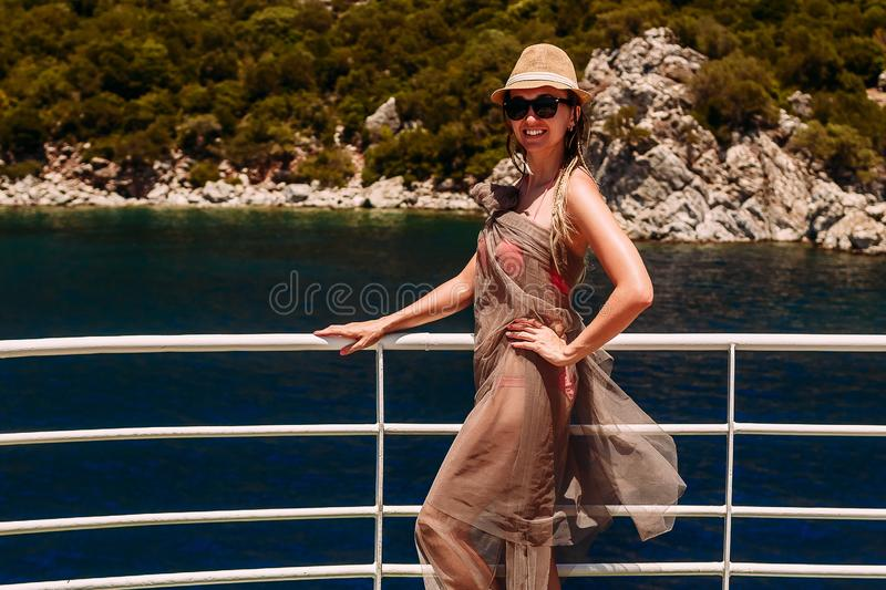 Young smiling woman in hat and swimsuit standing on yacht in sea and looking at camera, Turkey royalty free stock photo