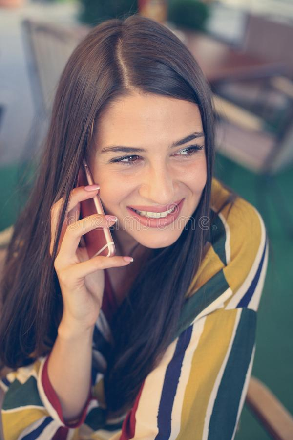 Young smiling woman having conversation on smart phone. royalty free stock image