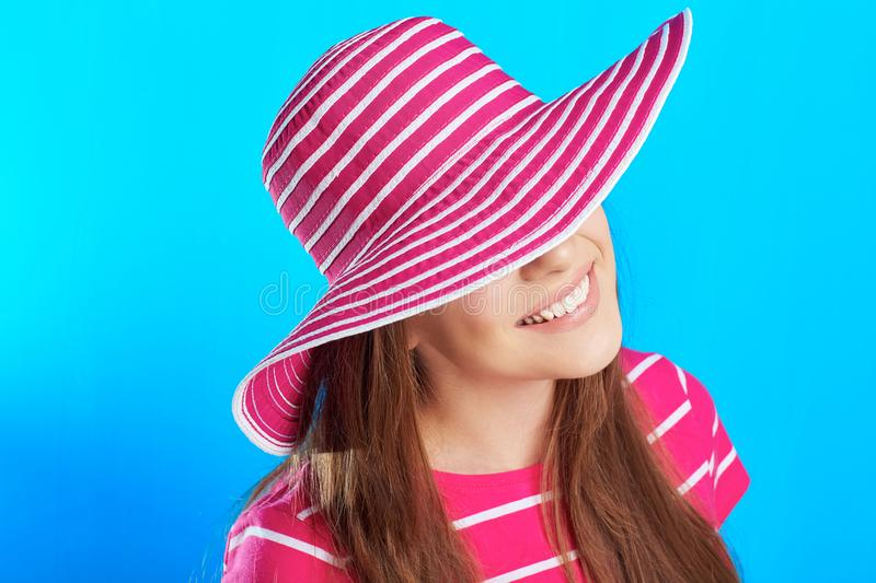 Young smiling woman hides his eyes behind a hat royalty free stock images
