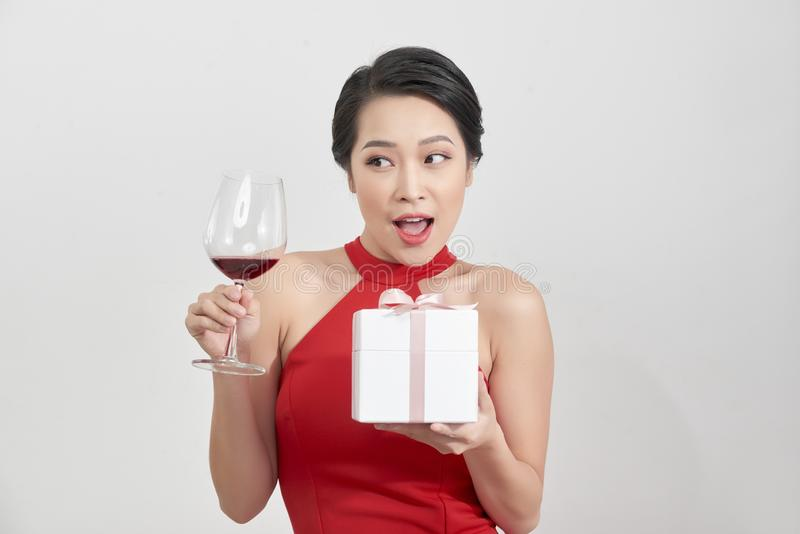 Young smiling woman hold christmas gift box. Isolated portrait of a beautiful girl with wine glass on studio background royalty free stock photos