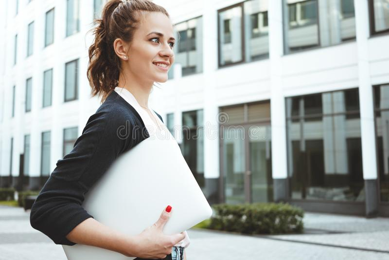 Young smiling woman hold in hand laptop and standing in business district. Success female student with personal computer and graduate work stand near stock photo