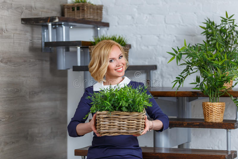 Young smiling woman holding box with green plants. Eco concept. stock photo