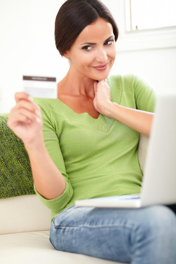 Young smiling woman holding a credit card. Vertical portrait of a young smiling woman holding a credit card while buying online royalty free stock photos