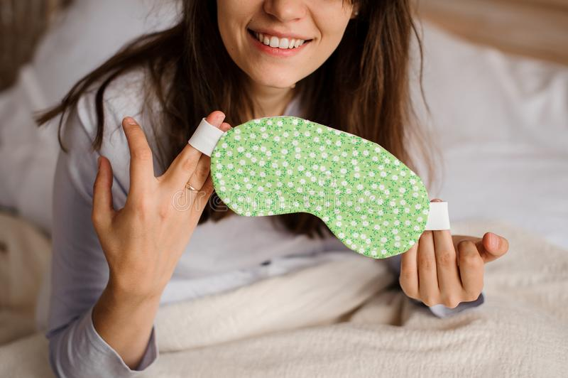 Smiling woman holding a cute sleep mask with a floral print stock photos