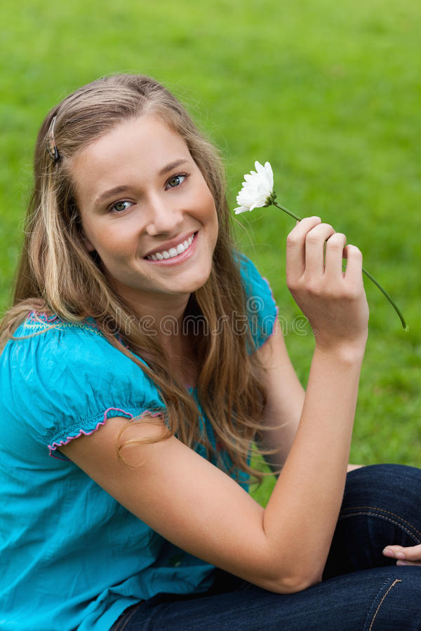 Young smiling woman holding a flower