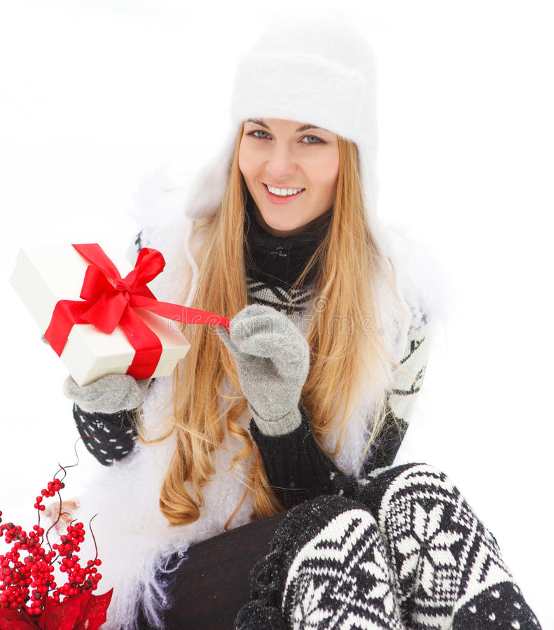 Young smiling woman holding gift. Decorated with red ribbon outdoors. Winter time royalty free stock photos