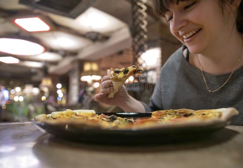 Young smiling woman holding a slice of pizza while sitting in a cafe, close-up royalty free stock photography