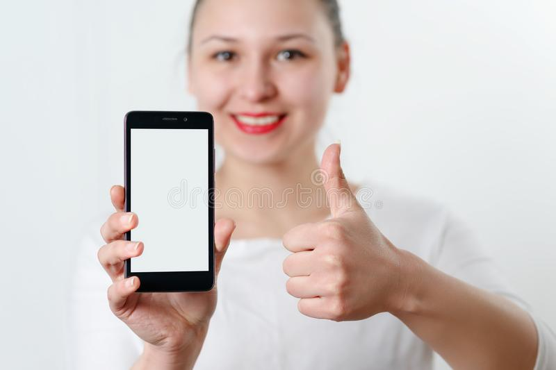 Young smiling woman holding smartphone vertically with white screen and with space for copyspace. Shows the gesture of the other. Hand thumb up. on a light stock images
