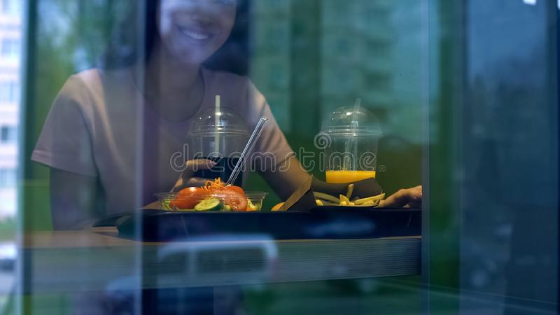 Young smiling woman holding soft drink, having lunch in fast food restaurant royalty free stock image