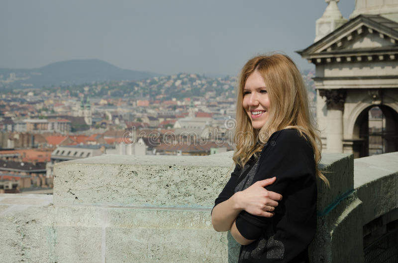 Young smiling woman looking at the cityscape. With admiration royalty free stock photography