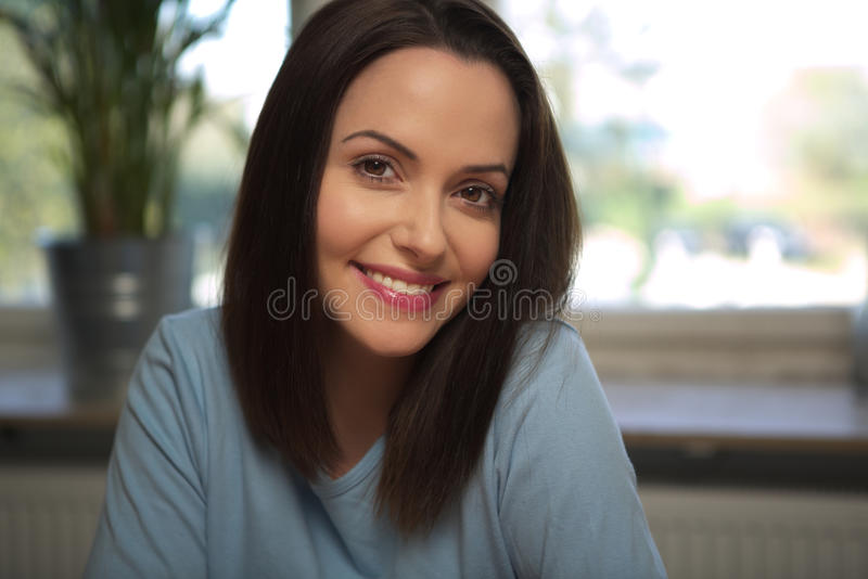 Young smiling woman looking straight ahead stock photo