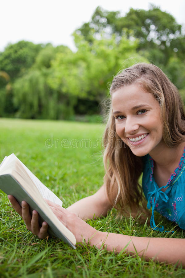 Download Young Smiling Woman Lying On The Grass In A Park Stock Photo - Image: 25331550