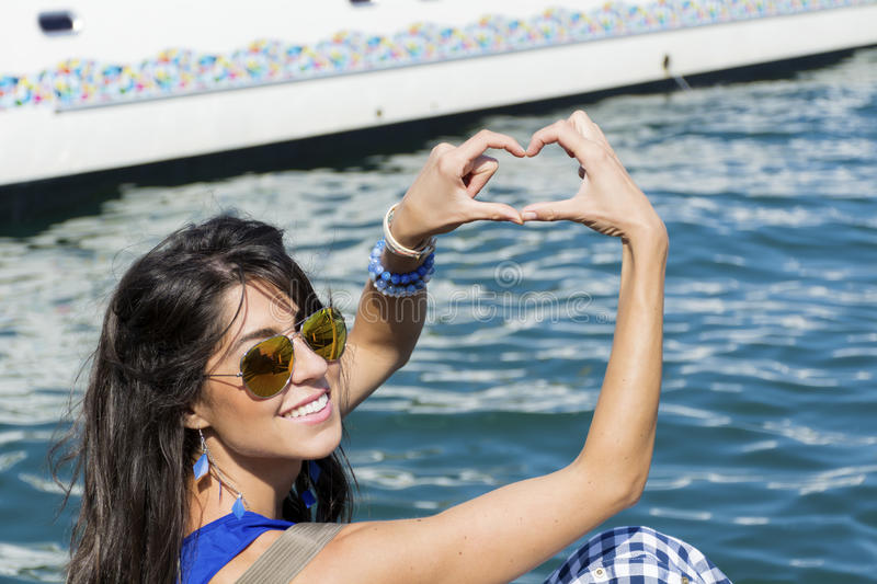 Young smiling woman making heart sign with the hands in Barcelona. Young smiling fashion woman making heart sign on a sea background stock image