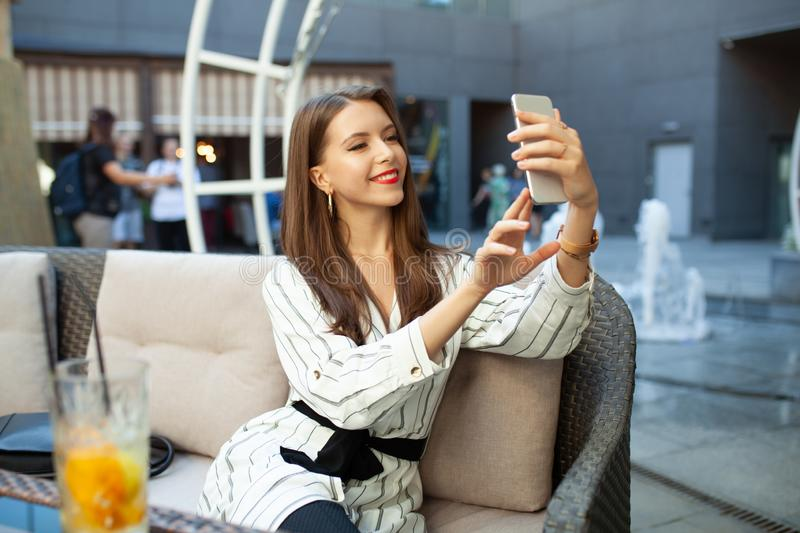 Young smiling woman making photo with smart phone digital camera while sitting in outdoor summer restaurant interior, happy female royalty free stock photo