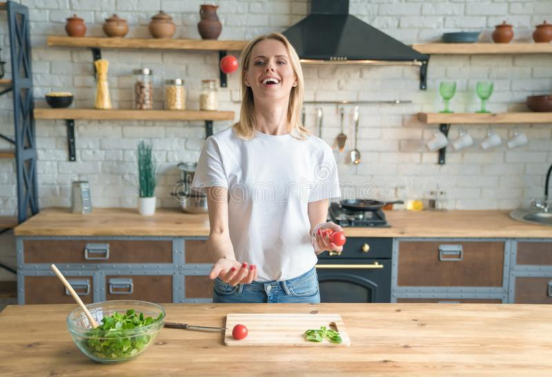 Young smiling woman making salad in the kitchen. Throwing up tomatoes and smiling. Having fun. Healthy food. vegetable salad. Diet stock images