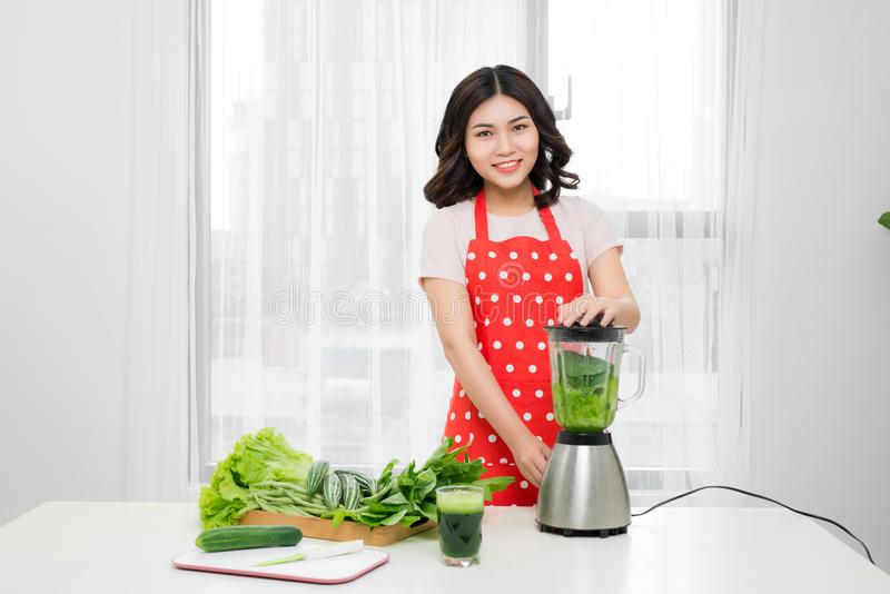 Young smiling woman making smoothie with fresh greens in the blender in kitchen at home. Healthy vegetarian smoothie for weight l. Oss and detox royalty free stock photos