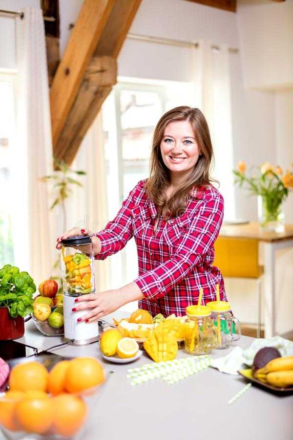 Young smiling woman making smoothie with fresh greens in the blender in kitchen at home royalty free stock images