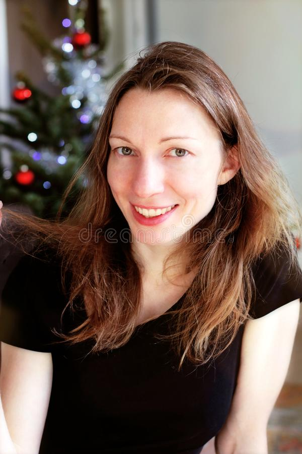 Young Smiling woman near Christmas tree. portrait cheerful royalty free stock photography