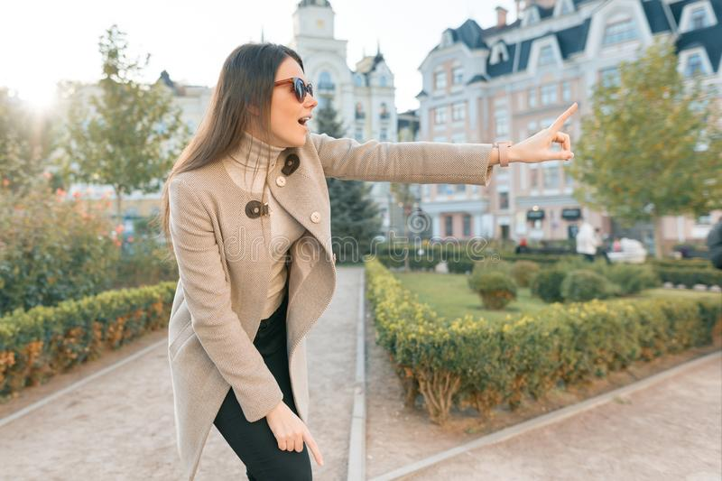 Young smiling woman pointing finger to the side, outdoor city style royalty free stock photo