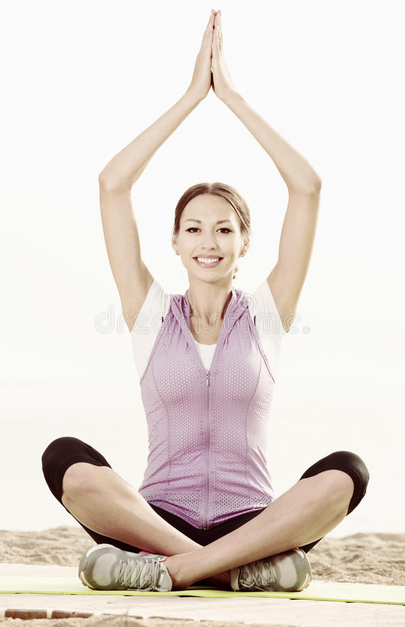 Young smiling woman practise yoga cross-legged. In morning by sea stock photo
