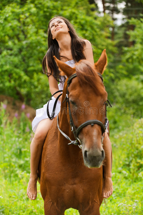 Young smiling woman riding horse royalty free stock image
