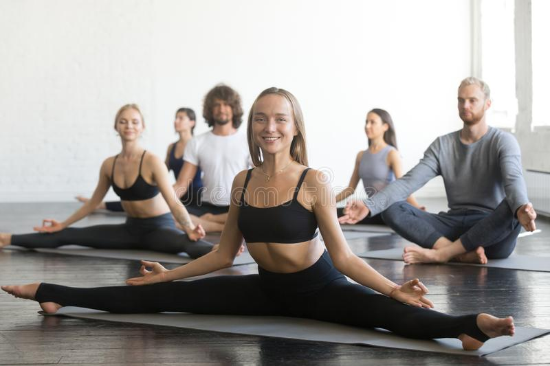 Young smiling woman in Samakonasana pose yoga lesson stock photo