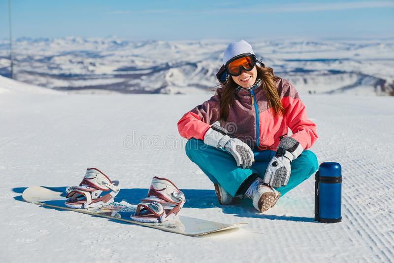 A young smiling woman sits on a mountain slope with a snowboard and a thermos stock photos