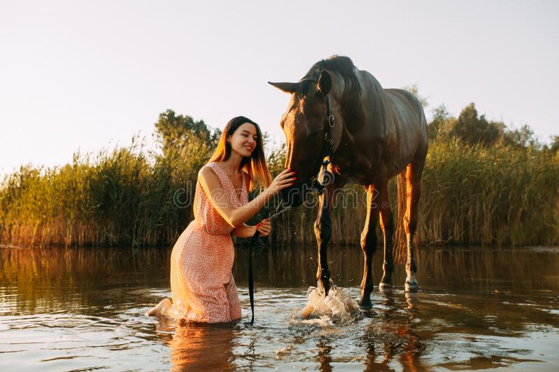 Woman sits next to the horse that produces splashes on the water. A young smiling woman sits next to the horse that produces splashes on the water at sunset stock photo