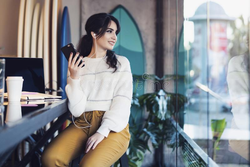 Young smiling woman sitting in cafe at table,looking out window, holding smartphone, listening to music on headphones. Lifestyle. Young smiling woman sitting in royalty free stock photography