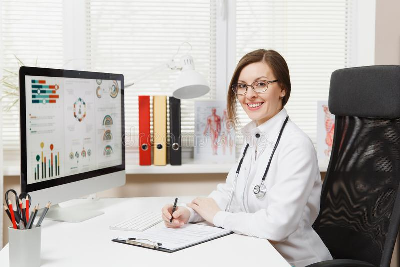Young smiling woman sitting at desk, working on computer with medical documents in light office in hospital. Female royalty free stock photo