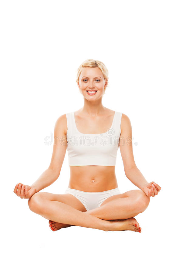 Young smiling woman sitting in lotus position. Young woman sitting in lotus position. Young woman doing yoga exercise stock photography